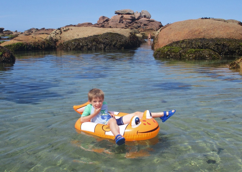 Child exploring the pink granite coast in an inflatable